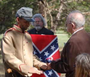 The Sons of Confederate Veterans present the flag to James H. Walker, the oldest living descendant of William T. Mclane.